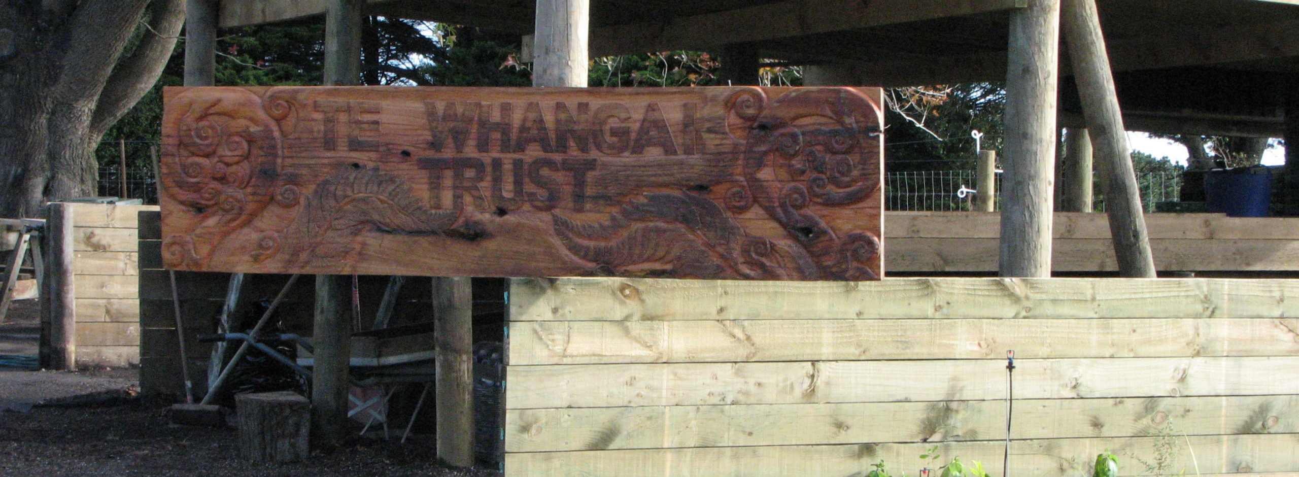 An image of Te Whangai Trust signage carved from a slab of macracarpa by trainees' Whanau.